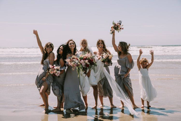 Bride in Grace Loves Lace Inca Gown with Boat Neck, Lace Sleeves and Low Back | Personalised Embroidered Veil by Daisy Sheldon | Bridesmaids in Grey Cold Shoulder Dresses by Rewritten | Bridal Party Bouquets of Burgundy and Blush Flowers with Foliage | Paddling in the Sea at Druidston Beach | Mykonos Rewritten Bridesmaid Dresses for an Epic Clifftop Coastal Wedding | Nic Ford Photography
