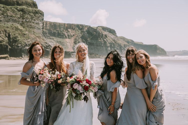 Bride in Grace Loves Lace Inca Gown with Boat Neck, Lace Sleeves and Low Back | Personalised Embroidered Veil by Daisy Sheldon | Bridesmaids in Grey Cold Shoulder Dresses by Rewritten | Bridal Party Bouquets of Burgundy and Blush Flowers with Foliage | Druidston Beach | Mykonos Rewritten Bridesmaid Dresses for an Epic Clifftop Coastal Wedding | Nic Ford Photography