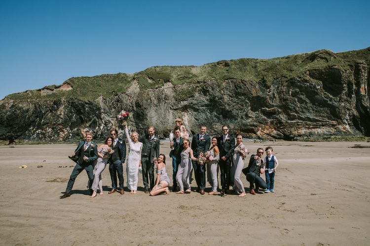 Bride in Grace Loves Lace Inca Gown with Boat Neck, Lace Sleeves and Low Back | Bridesmaids in Grey Cold Shoulder Dresses by Rewritten | Bridal Party Bouquets of Burgundy and Blush Flowers with Foliage | Groom in Three-Piece Grey Herringbone Suit with Burgundy Tie and Buttons | Groomsmen in Mismatched Navy Suits with Blush Pink Ties | Druidston Beach | Mykonos Rewritten Bridesmaid Dresses for an Epic Clifftop Coastal Wedding | Nic Ford Photography