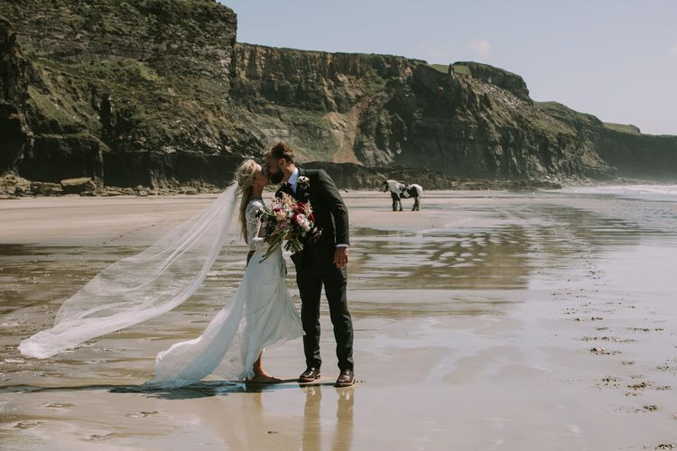 Bride in Grace Loves Lace Inca Gown with Boat Neck, Lace Sleeves and Low Back | Personalised Embroidered Veil by Daisy Sheldon | Bridal Bouquet of Burgundy and Blush Flowers with Foliage | Groom in Three-Piece Grey Herringbone Suit with Burgundy Tie and Buttons | Blush Buttonhole | Druidston Beach | Mykonos Rewritten Bridesmaid Dresses for an Epic Clifftop Coastal Wedding | Nic Ford Photography