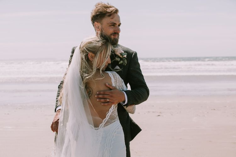 Bride in Grace Loves Lace Inca Gown with Boat Neck, Lace Sleeves and Low Back | Personalised Embroidered Veil by Daisy Sheldon | Aurora Hair Comb by Tilly Thomas Lux | Groom in Three-Piece Grey Herringbone Suit with Burgundy Tie and Buttons | Blush Buttonhole | Druidston Beach | Mykonos Rewritten Bridesmaid Dresses for an Epic Clifftop Coastal Wedding | Nic Ford Photography