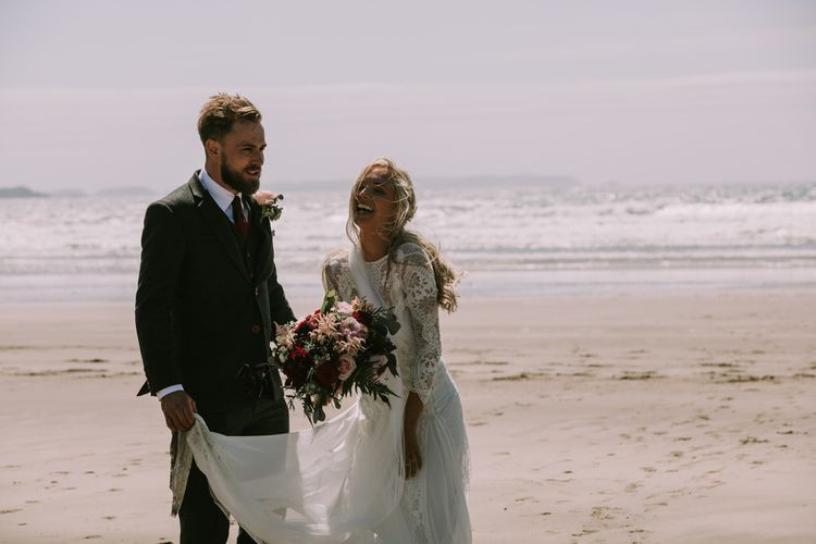 Bride in Grace Loves Lace Inca Gown with Boat Neck, Lace Sleeves and Low Back | Personalised Embroidered Veil by Daisy Sheldon | Groom in Three-Piece Grey Herringbone Suit with Burgundy Tie and Buttons | Blush Buttonhole | Druidston Beach | Mykonos Rewritten Bridesmaid Dresses for an Epic Clifftop Coastal Wedding | Nic Ford Photography