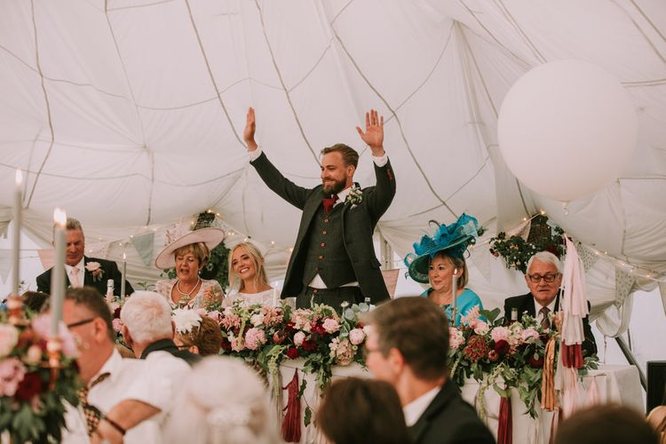 Groom in Three-Piece Grey Herringbone Suit with Burgundy Tie and Buttons | Blush Buttonhole | Marquee with Draped Ceiling at The Druidstone | Top Table Runner of Blush and Burgundy Flowers with Foliage | Pastel Bunting | Fairy Lights | Grey Tapered Candles | Giant White Balloons with Grey, Blush and Burgundy Tassels | Mykonos Rewritten Bridesmaid Dresses for an Epic Clifftop Coastal Wedding | Nic Ford Photography