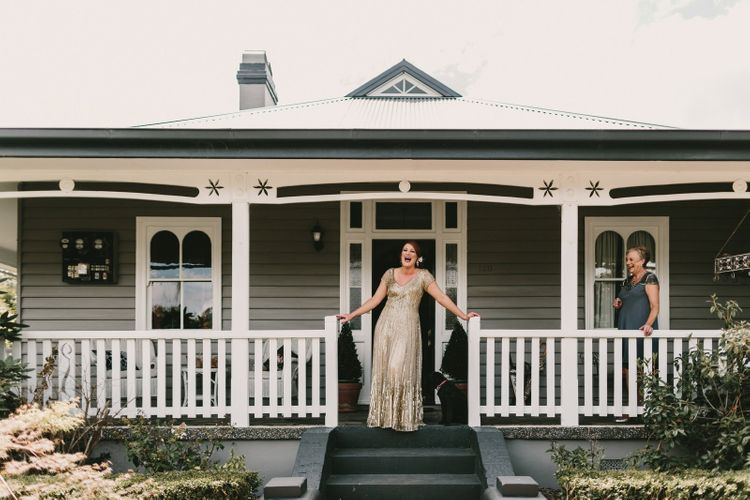 Bride Standing on a Porch in Her Sequin Gold Wedding Dress