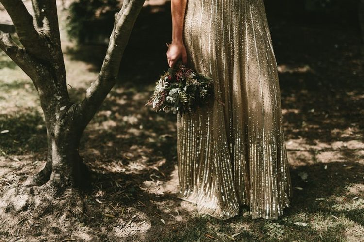 Bride Holding Her Protea Wedding Bouquet Next to Her Sequin Gold Wedding Dress