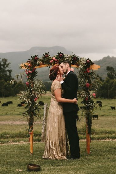 King Protea Floral Altar with Bride in Sequin Gold Wedding Dress and Groom  in Dark Suit Kissing