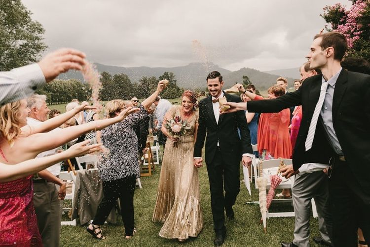 Confetti Moment  with Bride in Sequin Gold Wedding Dress and Groom  in Dark Suit and Wood Bow Tie