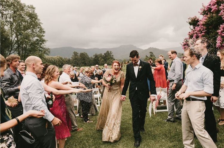 Confetti Exit  with Bride in Sequin Gold Wedding Dress and Groom  in Dark Suit and Wood Bow Tie