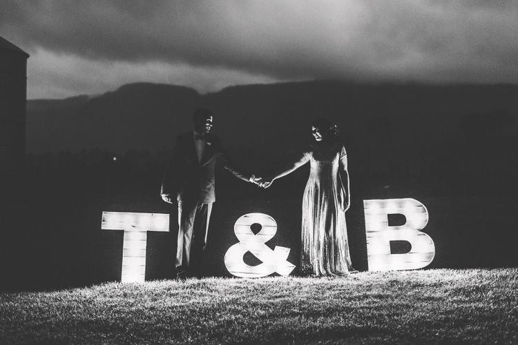 Bride and Groom Standing Next to Giant Initial Lights