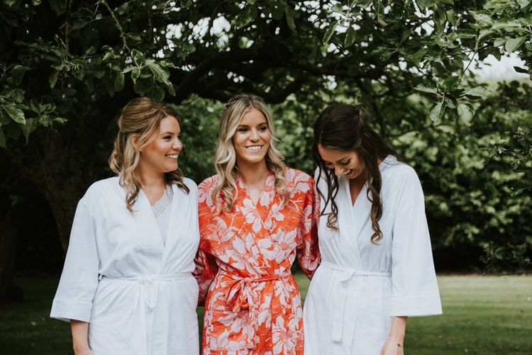 Bridal party in getting ready robes for wedding with wildflower bouquets