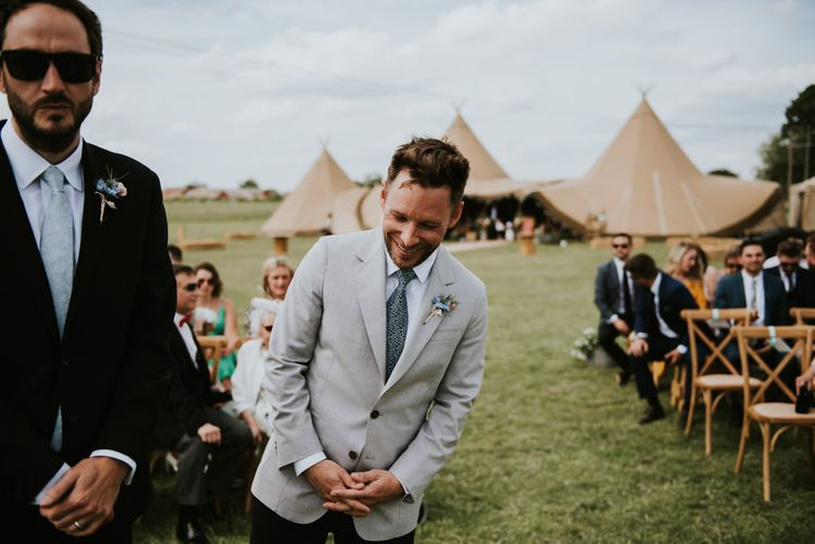 Groom waits for bride at outdoor ceremony in front of tipi