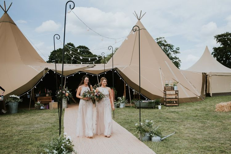 Bridesmaids in pink floral dresses enter ceremony through tipi