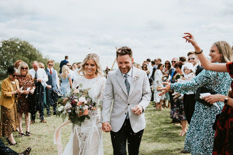 Confetti exit for bride and groom with wildflower bouquet