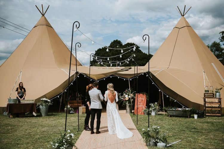 Bride and groom make their way to tipi reception