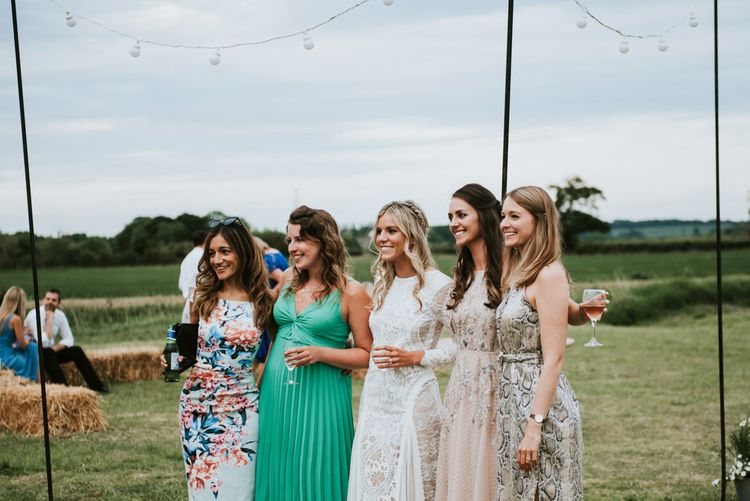 Bride enjoys time with her guests outside tipi reception