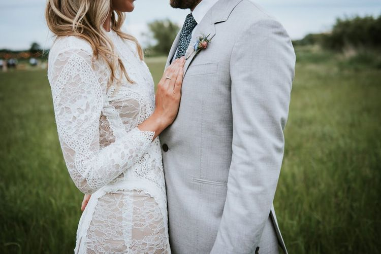 Bride dress lace detail and pale coloured dinner jacket for groom