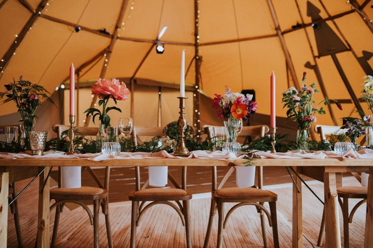 Tipi wedding decoration with wildflower bouquet for bride