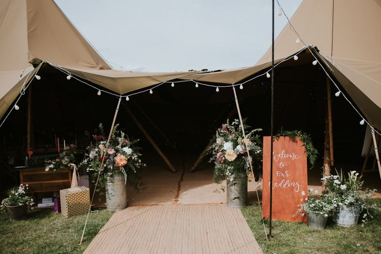 Tipi wedding entrance with wedding flowers and wildflower bouquet