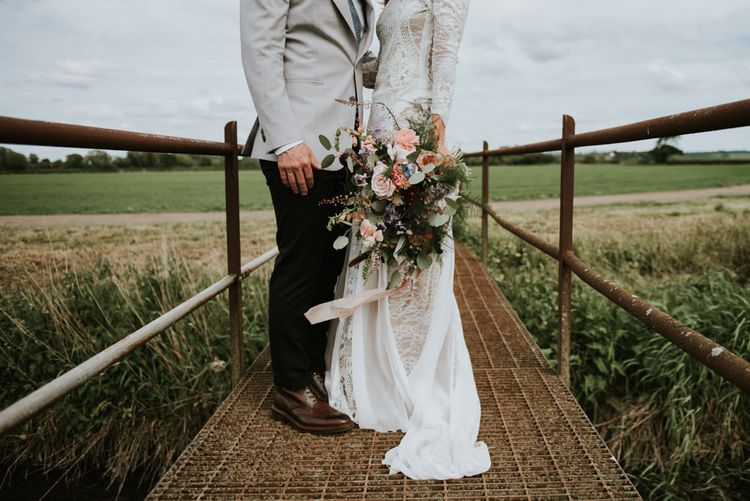 Wildflower bouquet, grace loves lace bride dress and grooms light jacket