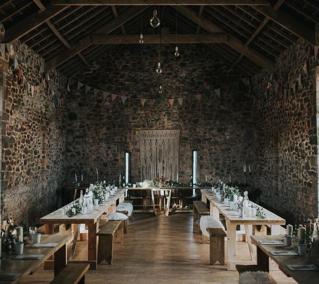 Wedding Barn At Carhyn Farm With Wooden Trestle Tables / Image by Jo Greenfield Photographer
