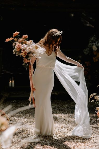 Bride in Fitted Wedding Dress and Wedding Veil Holding an Orange Flower Bouquet