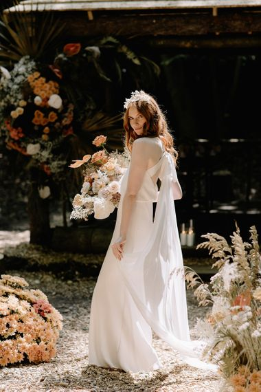 Bride in Fitted Wedding Dress with Tie Back Holding a Dried Flower Bouquet