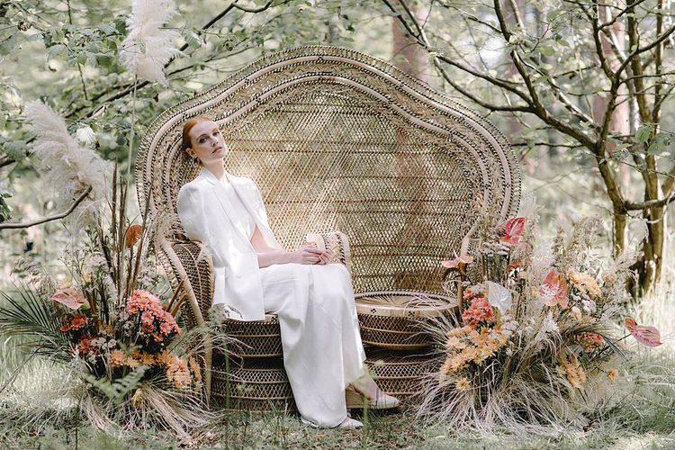 Bride in Blazer Sitting on a Double Peacock Chair in the Woods