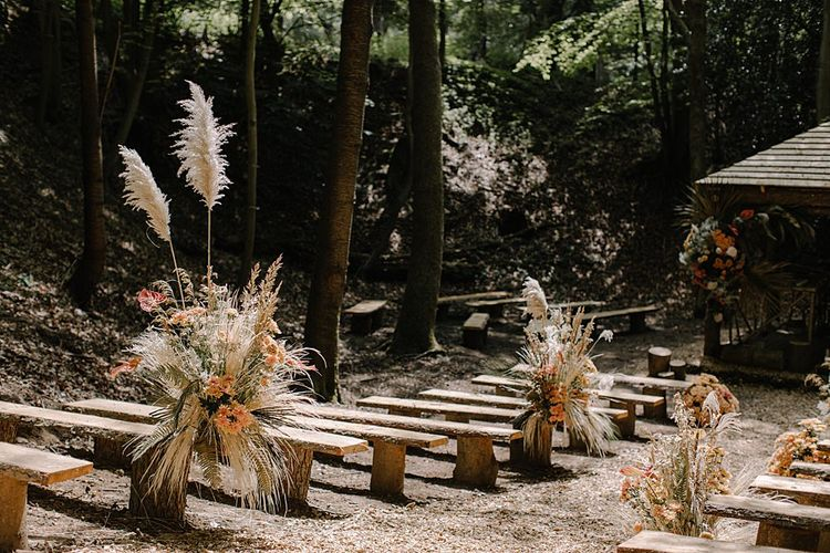 Outdoor Woodland Ceremony with Dried Grass and Orange Flower Arrangements