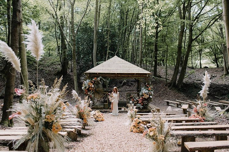Outdoor Woodland Ceremony with Wooden Benches, and Hut Decorated in Floral Arrangements