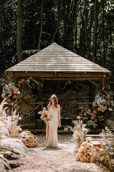 Bride in Fitted Weddng Dress at Woodland Wedding Ceremony Decorated in Orange and Dried Flower Arrangements