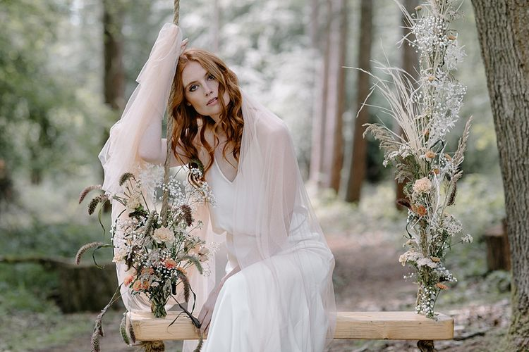 Beautiful Bride in a Fitted Wedding Dress and Blush Tulle Stole Sitting on a Swing in the Woodland