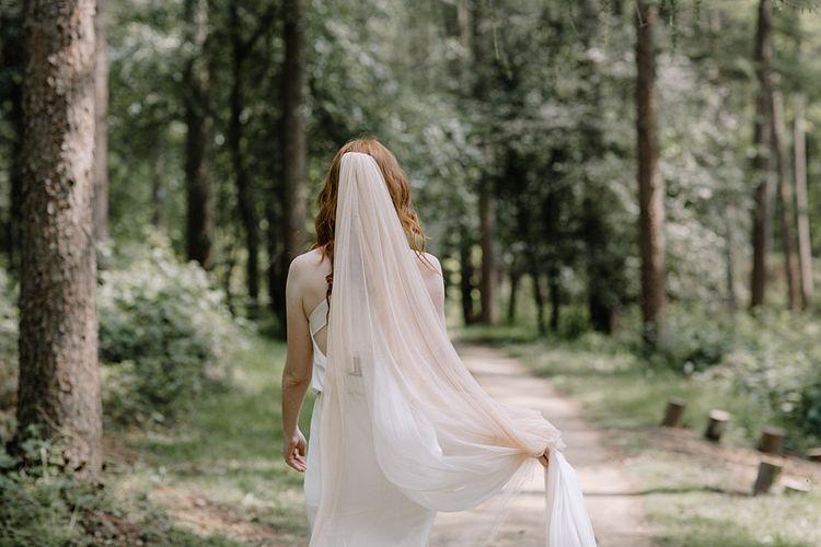 Bride Walking in the Woodland with Blush Wedding Veil