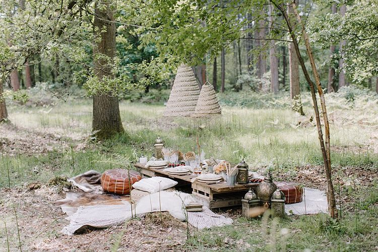 Relaxed Grazing Table in the Woodland with Poufs, blankets and Cushions