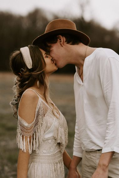 Boho Couple Kissing with Bride in Cold Shoulder Lace Dress and Groom in Fedora Hat