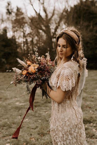 Boho Bride in Lace Wedding Dress Holding a Boho Wedding Bouquet