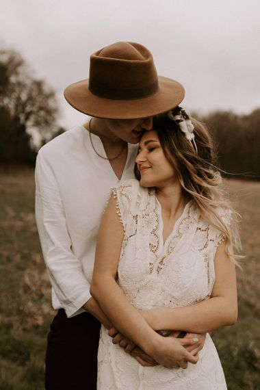 Groom in Fedora Hat Kissing His Boho Bride in a Lace Wedding Dress