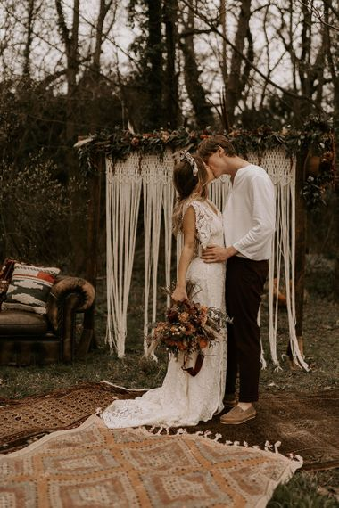 Boho Bride in Lace Wedding Dress Kissing Her Groom in Casual Shirt and Trousers at the Altar of Macrame Backdrop and Persian Rug Floor