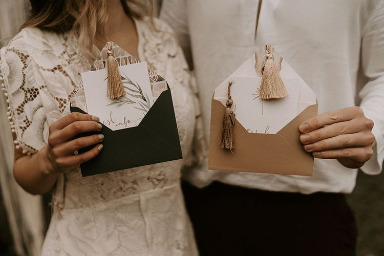 Bride and Groom Holding the Wedding Invitation with Tassel Detail