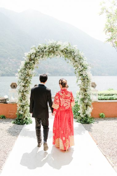 Chinese Tea Ceremony  Wedding White and Green Floral Arch with Bride in Traditional Chinese Red Dress and Groom in Black Suit