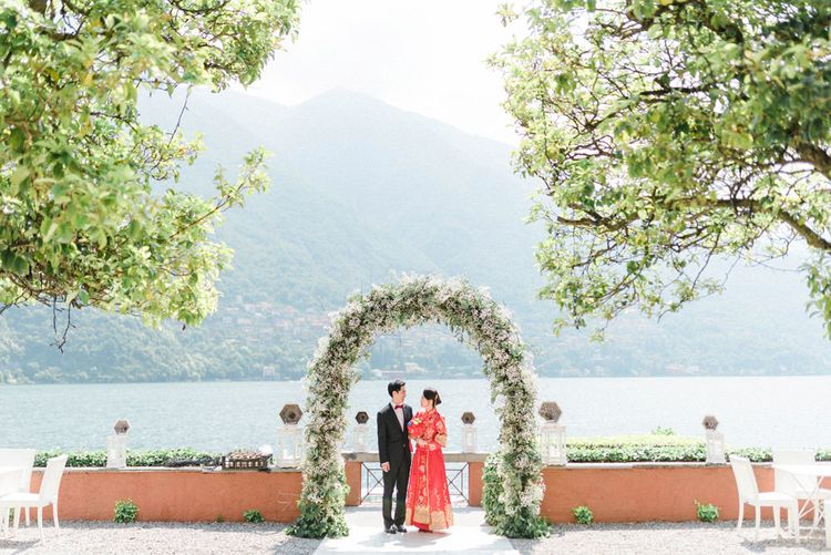 Chinese Tea Ceremony Wedding White and Green Floral Arch with Asian Bride in Traditional Chinese Red Dress and Groom in Black Suit