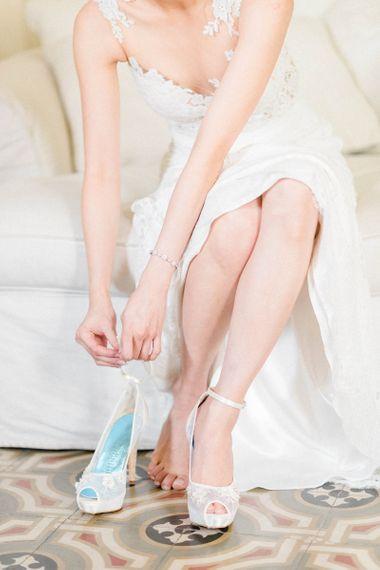 Bride in Anna Kara Wedding Dress Putting on Her Freya Rose Wedding Shoes