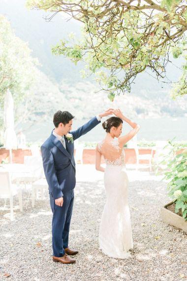 Groom in Navy Suit Twirling his Bride in Fitted Anna Kara Wedding Dress