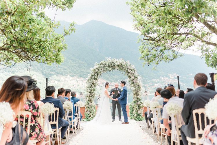 Outdoor Wedding Ceremony with Bride and Groom Saying their Vows in Front of a Gypsophila Floral Arch