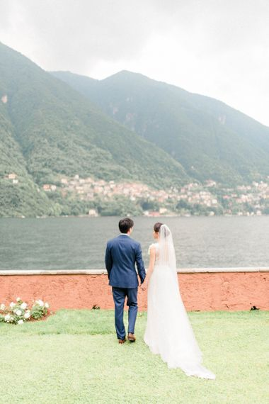 Bride in Fitted Anna Kara Wedding Dress and Groom in Navy Suit Looking Out Over Lake Como