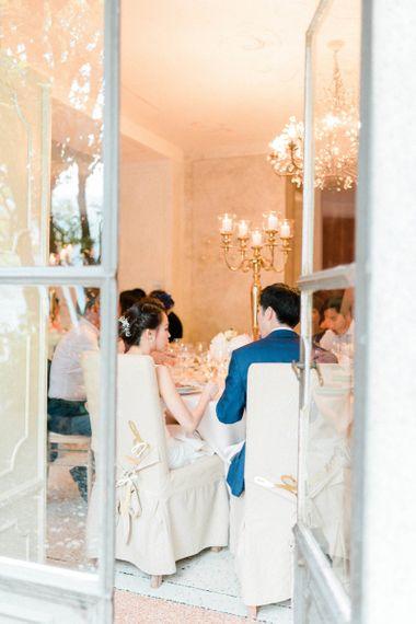 Bride in Anna Kara Wedding Dress and Groom in Three-piece Navy Wedding Suit At Their Wedding Breakfast
