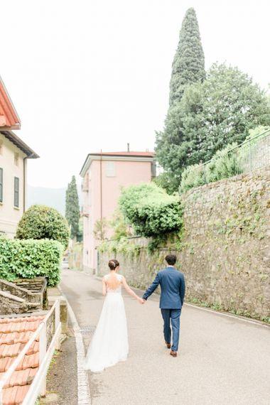 Bride in Anna Kara Wedding Dress and Groom in Three-piece Navy Wedding Suit Holding Hands
