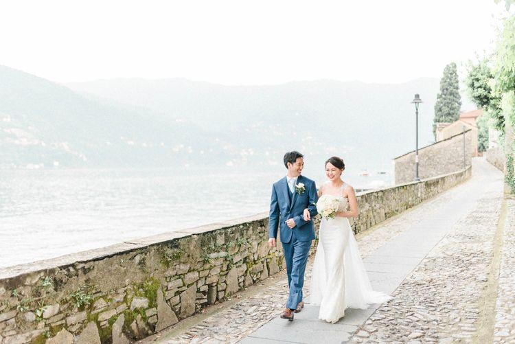 Bride in Anna Kara Wedding Dress and Groom in Three-piece Navy Wedding Suit Walking Next to Lake Como