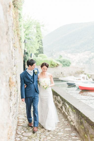 Bride in Anna Kara Wedding Dress and Groom in Three-piece Navy Wedding Suit Arm in Arm