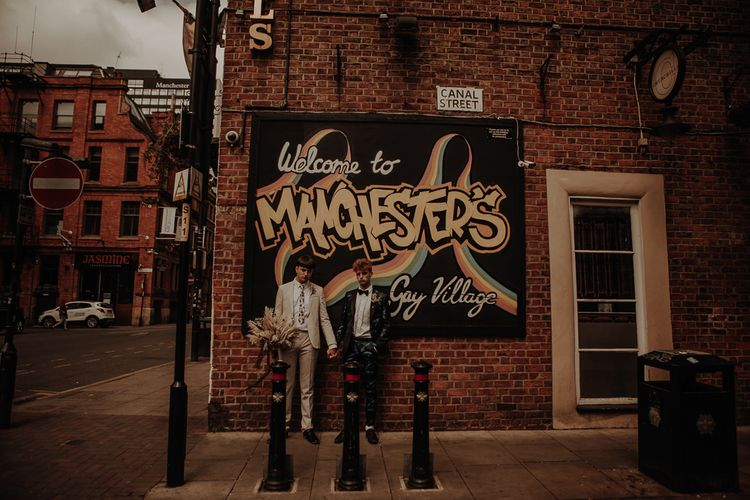 Gay couple standing in front of wall art in Manchester's Gay Village