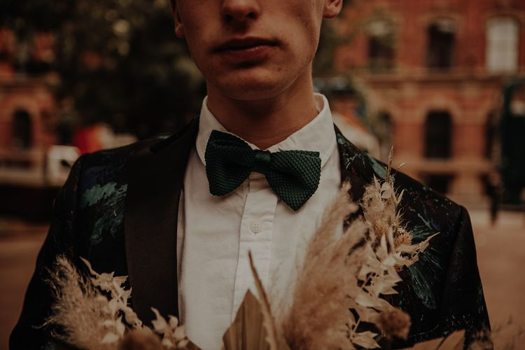 Groom in green bow tie with patterned suit
